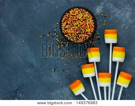 Candy corn marshmallow pops and sugar sprinkling - Halloween party or thanksgiving concept background with copy space