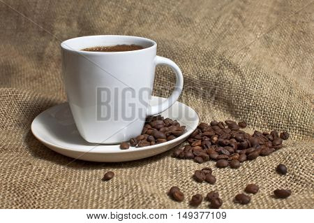 Cup of coffee and coffee beans on jute background