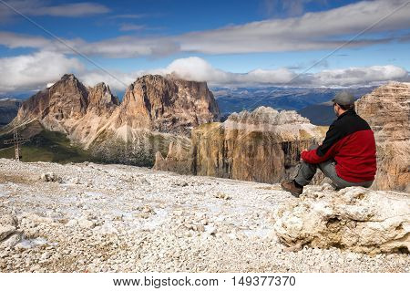 Young man looking at Punta Grohmann Cinquue Dita Sasso Lungo Piz Ciavaces from Sass Pordoi Dolomites Italy Europe