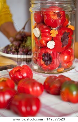 Jar with fresh tomato peppers filled with grapes prepared to be pickled. Pickled peppers filled with grapes is a typical recipe from Romania.