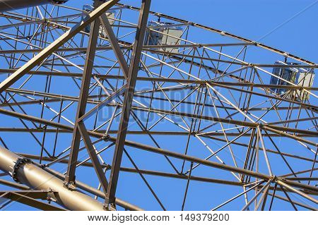Metalwork details of ferris wheel at the blue sky background
