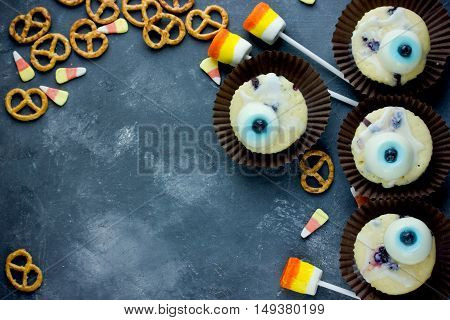 Halloween fun food - eye muffins cookies candy corn marshmallow pops on a stone background top view of blank space for text