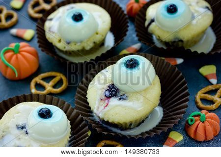 Funny idea for Halloween food - cupcake with edible eyes on background with candy corn and cookies festive treat for children