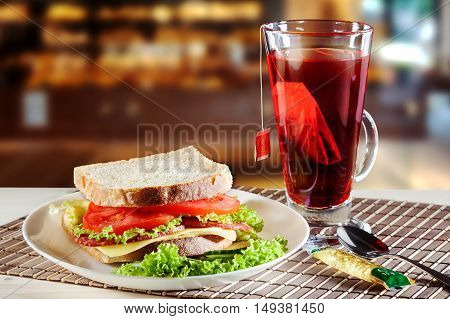 Sandwich with salami cheese and salad and red fruit tea.