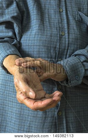 Elderly hand measuring her own arm pulse. Selective focus