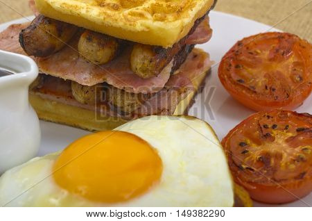 Waffle Stack Breakfast Breakfast of waffles, bacon, egg, sausage in a stack,  a side of tomato, and sunny side up egg sat on the hash browns with a jug of maple syrup