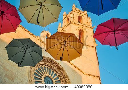 Colorful Umbrellas Against Gothic Cathedral.