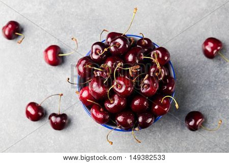 Fresh ripe black cherries in a blue bowl on a grey stone background Top view Copy space.