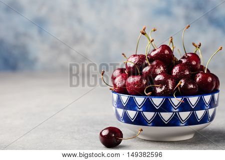 Fresh ripe black cherries in a black bowl on a grey stone background Copy space.