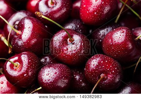 Fresh ripe black cherries on a blue stone background Top view Close up.