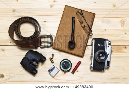 Still life with retro object. Book with compact old camera compass cigarette lighter bullet belt glasses pipe binocular on wood table.