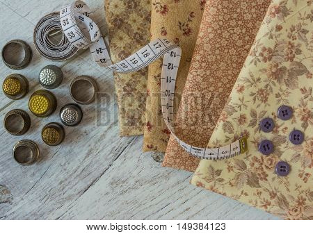 vintage cloth measuring tape old thimbles buttons lie on a light wooden table. Top view