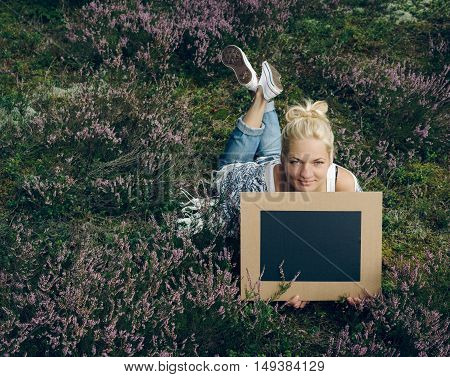 Young woman lying on the grass and holding a slate. Space for text. Chalkboard.
