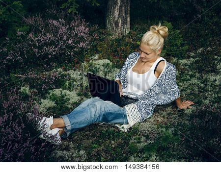Young woman sitting on the grass in the forest and looking computer. Woman using laptop at outdoor.
