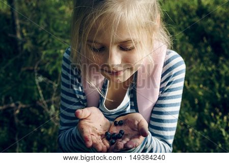 Little girl standing in the woods with stained mouth holds blueberries. Autumn time