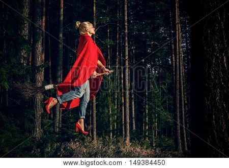 Modern witch blond in jeans and a red cape flying on a broom through the forest. Levitation. Halloween holiday.