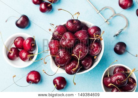 Fresh ripe black cherries in a white bowl on a blue stone background Top view.