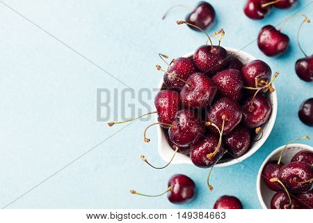 Fresh ripe black cherries in a white bowl on a blue stone background Copy space Top view.