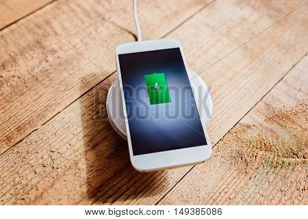 White Smartphone Charging On A Charging Pad.