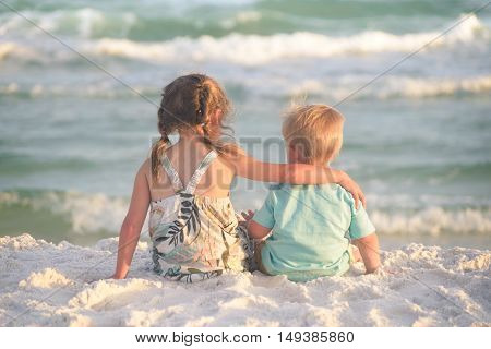 Sister and brother hugging on the beach