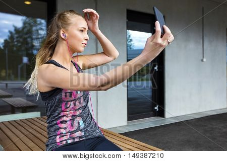 Beautiful young woman in sportswear taking selfie through smartphone while sitting on bench
