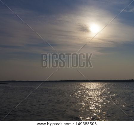 Thin clouds obscuring the sun temporarily over a Saksatchewan Canada lake
