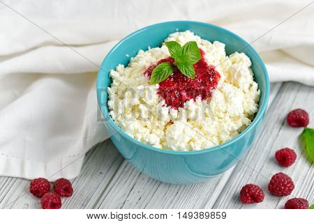 Cottage Cheese In Blue Bowl With Raspberries Jam And Mint On Wooden Background