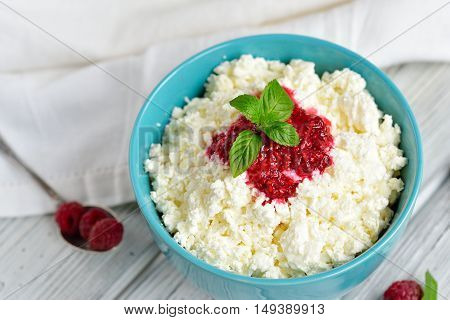 Close Up Cottage Cheese In Blue Bowl With Raspberries Jam And Mint On Wooden Background