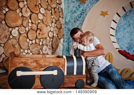 Young Happy Father With Son Playing In Decor Room With Children Wooden Locomotive
