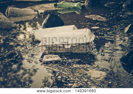 Water pollution - Plastic and foam garbage floating on the surface of the river - Environmental problem caused by human activity