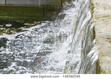 Water cascades down manmade waterfall along Boston's Harborwalk