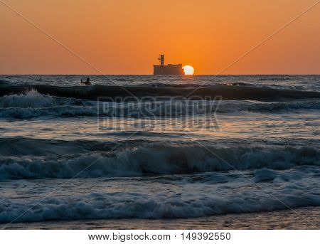 the sun rises over the horizon of the sea and the boy enjoys the rising sun