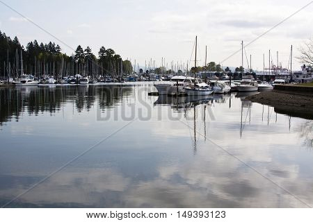 Looking at the marina at the Royal Vancouver Yacht Club full of yachts and sailboats on a bright, sunny spring day with reflections in the clear water.