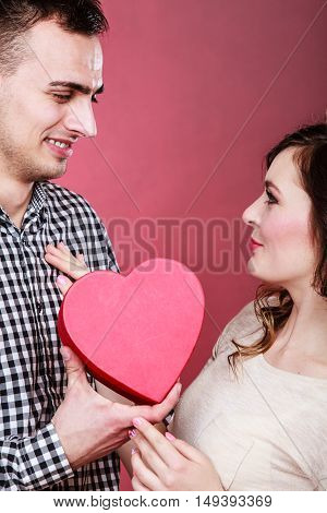 Romantic couple on valentines day. Happy joyful man and woman holding heart shape box looking in each other eyes. Love concept.