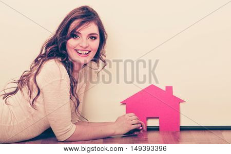 Smiling young woman girl holding paper house dreaming about new home. Housing and real estate concept. Instagram filtered.
