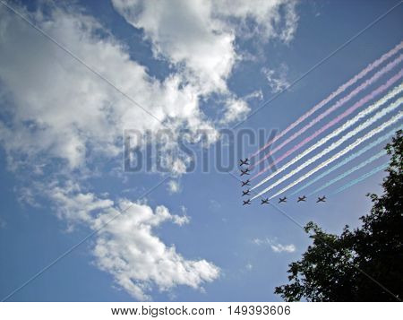 Royal Air Force Red Arrows aerobatic display team in flight with red blue and white smoke. Nine aircraft. Background of blue sky with white clouds and trees beneath.