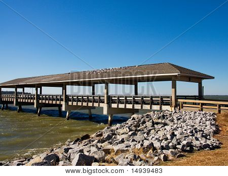 Pier By Rocks With Seagulls On Roof