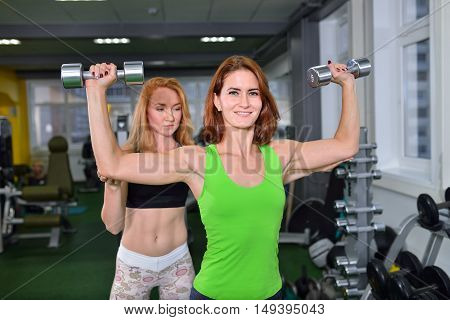sport, fitness, bodybuilding, lifestyle concept - Woman doing chest and shoulder dumbbell press with personal coach assisting her.