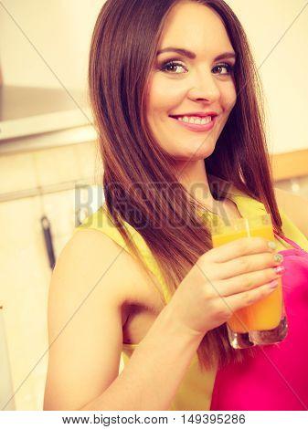 Woman In Kitchen Drinking Fresh Orange Juice