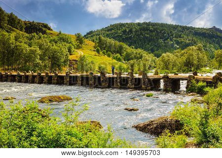 Tourist woman standing on stone slab bridge Terland Klopp in Norway Dalane region.