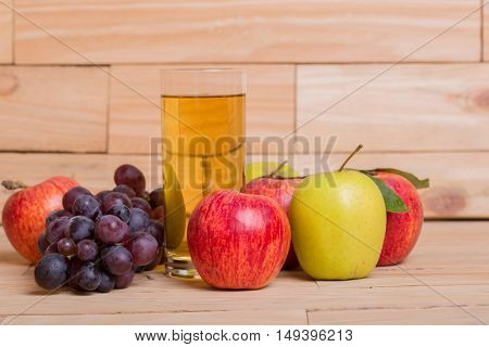 Glass of apple juice with fruits on wooden background