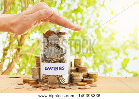Coins stack and hand protection for saving finance conceptbusiness backgroundmoney content and selective focus.