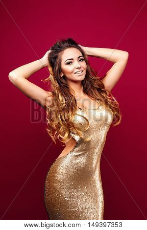 Portrait of young seductive girl in golden dress touching her chin and looking at camera against red background