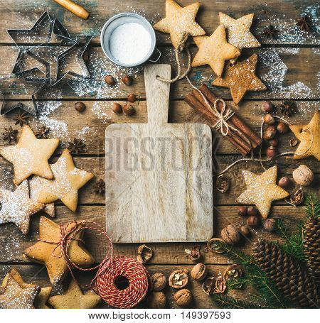 Christmas, New Year background. Gingerbread cookies, sugar powder, nuts, spices, baking molds, fir-tree branch, pine cones on rustic background, serving wooden board in center, top view, copy space