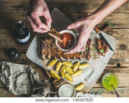 Man eating roasted pork ribs with potato pieces, garlic, rosemary and green herb sauce on rustic wooden table. Man' s hands dipping piece of meat to ketchup in white bowl , top view