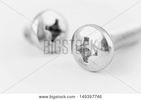 horizontal image of two small silver screws isolated on white background