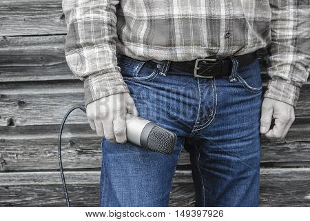 horizontal color selective image of the bottom torso of a man holding a microphone in his hand resting on his thigh with the background being a vintage sepia color and his jeans a denim blue.