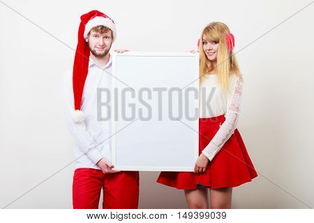 Couple woman and man holding empty blank banner with copy space. Pretty girl in santa claus hat and man. Christmas xmas advertisement.