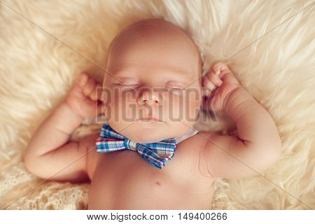 Sleeping newborn baby lying with the bow tie on a white fur rug. Little gentleman resting after a hard day