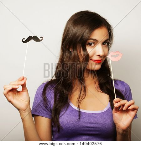 Young woman wearing fake mustaches.
